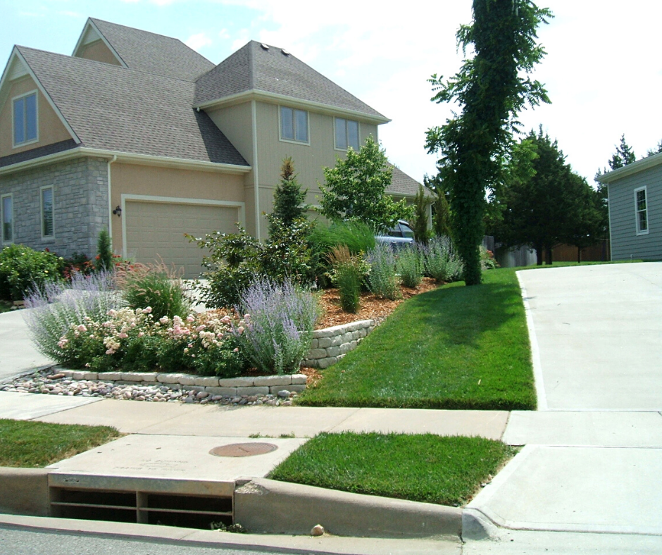 New landscaping with flowers, bushes, trees, grass, stones, and more